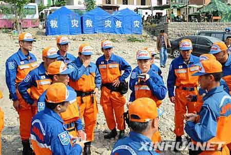 """由于距离山体滑坡搜救地点5公里处道路没有打通,搜救人员只能暂时原地待命。日本救援人员表示:""""只要有一线希望,我们就会努力到最后一刻。"""" 这是日本救援人员在紧急协商是否更换搜救地点。新华社记者 李涛 摄"""