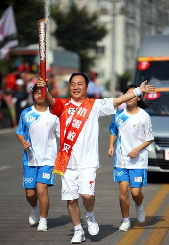 5月17日,火炬手手持火炬进行传递。当日,北京奥运会圣火在浙江温州传递。新华社记者邢广利摄