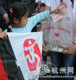 小女孩捐款后获得了一只美丽的奥运风筝。