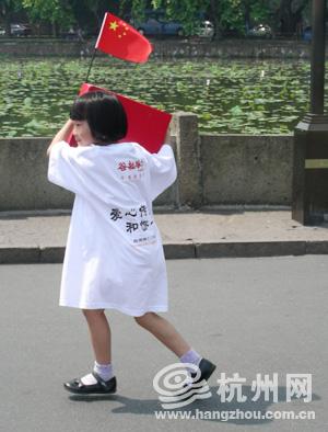 小义工高举着国旗和捐款箱,她也想出一份自己的力。