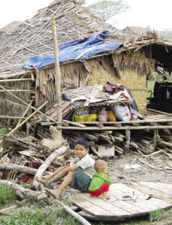 5月14日,在缅甸仰光市郊,两名儿童在棚子旁边等待救援。新华社发