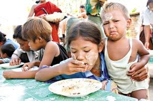 抱着小弟弟用餐的缅甸小女孩。目前,在很多城镇,受灾儿童都盼望着救援车辆,希望领取面包和衣物。
