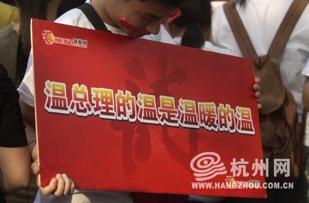 """火炬传递现场,群众打出了""""温总理的温是温暖的温""""的红色标语。来源:杭州网"""