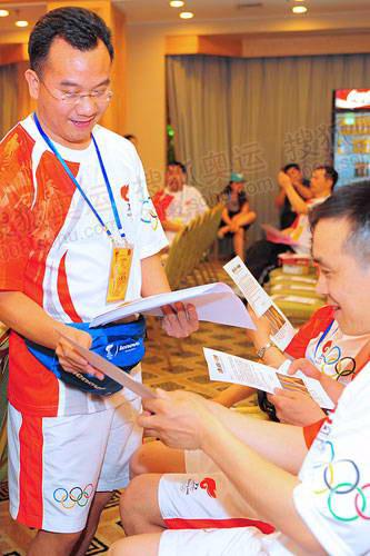 搜狐副总裁、火炬手陈陆明帮着分发《致21880名北京奥运会火炬手的倡议书》 摄影/程宫