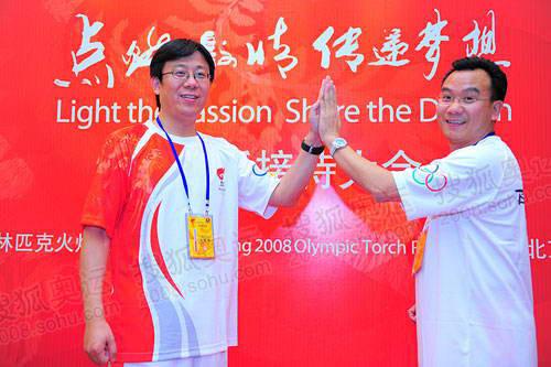 搜狐副总裁陈陆明和联想副总裁周庆彤两名火炬手演示团结一心手势的分解动作 摄影/程宫