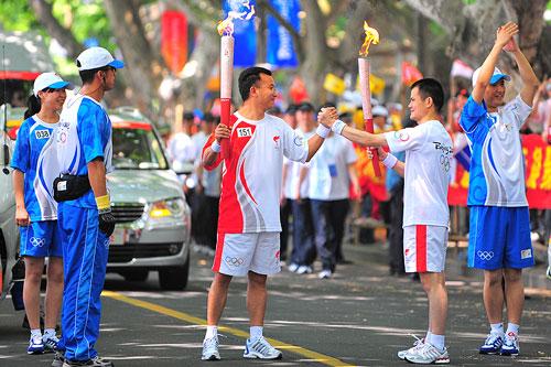 杭州火炬传递-03-CG1_3432--交接棒时火炬手自发的抗震救灾团结一心握拳手势