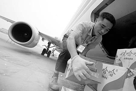 图为本报首批爱心航线物资抵达成都双流机场后,机场工作人员正在卸货 摄/记者杨威