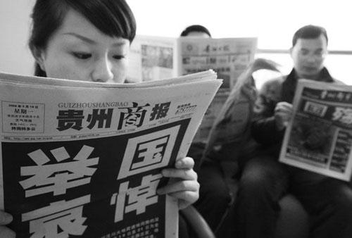 5月19日,一位贵阳市民正在阅读当天的报纸。这是对四川汶川大地震遇难者举行全国哀悼日的第一天,全国各大网站和报纸纷纷在首页或头版以黑体字公布这一消息,向汶川地震遇难者志哀。