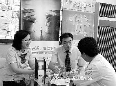 卓先生(右一)成为江门邮政储蓄银行小额贷款的首位客户。