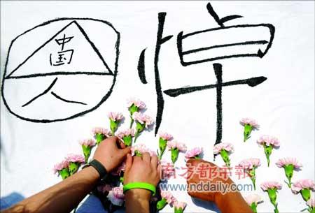 5月19日,全国哀悼日。成都,天府广场。几个市民在白布上写上字,插满花,悼念死去的同胞。田飞摄