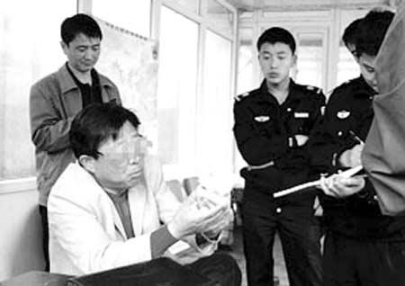 民警在向失主薛先生(手中拿钱者)询问情况。