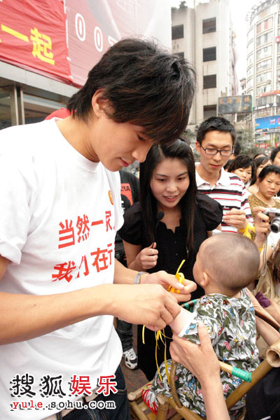 何润东为年龄最小的募捐者系上黄丝带