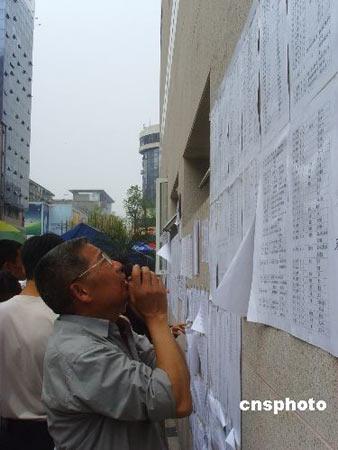 5月16日下午,绵阳市中心医院将当天新收救的受伤灾民名单贴在墙上,一男子焦急地在名单上寻找亲人的名字。 中新社发 霍潺 摄