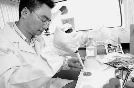王海明博士在流动检验车上对水源样本进行检验。 本报特派记者 徐彦 叶寒青 王颖 摄