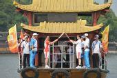 图文:奥运圣火在嘉兴传递 火炬手南湖船上交接