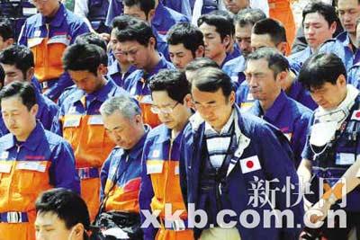 5月19日,正在北川县执行搜救任务的日本救援人员在默哀,悼念汶川大地震遇难者。