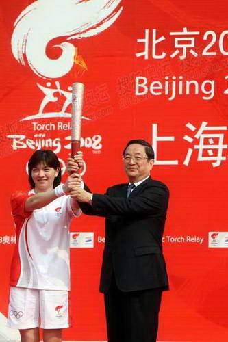 中共中央政治局委员、上海市委书记俞正声将祥云火炬移交给第一棒火炬手1992年西班牙巴塞罗那奥运会游泳冠军庄泳