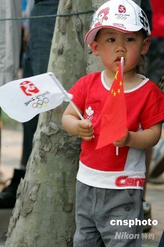 """5月23日,一位身着奥运""""行头""""的上海儿童,在街头观看奥运圣火传递。 中新社发 汤彦俊 摄"""