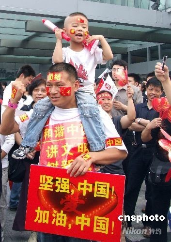 5月23日,北京奥运圣火在上海开始传递。众多市民一大早就来到火炬传递沿途守侯,迎接奥运圣火,为抗震救灾鼓劲加油。 中新社发 段更强 摄