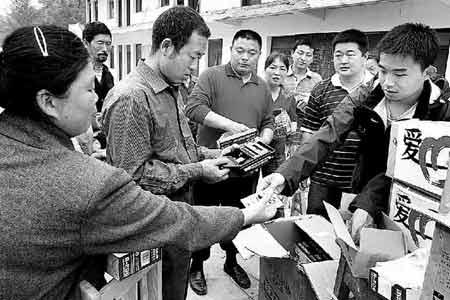 在香水乡元坪村,本报记者张子渊(右一)为灾区群众分发爱心航线物资中的收音机和电池