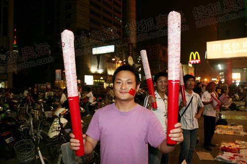 火炬到来的前夜,江苏南通市市民冒雨在街头欢庆圣火的到来,图为南通市民冒雨在街头高举塑料充气火炬,迎接圣火到来。