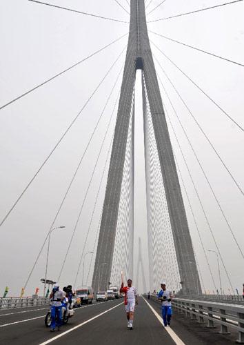 5月25日,火炬手朱相桂在苏通大桥上进行传递。当日,北京奥运会圣火在江苏南通传递。 新华社记者安治平摄