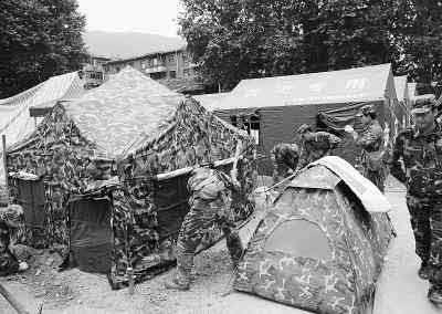 照片说明:5月20日,解放军官兵在四川省青川县城为受灾群众搭建临时帐篷。当日下午,青川县城后山出现山体裂缝,威胁5万受灾群众和救灾部队的安全。 新华社记者 蔺以光摄