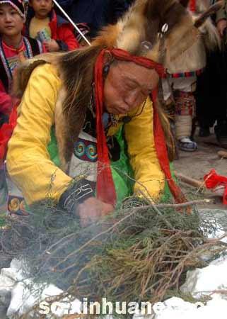 资料图片:2006年11月5日,一名羌族村民用白石取火后引燃树枝。