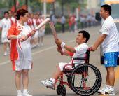 图文:奥运圣火泰州传递 残疾人火炬手交接火炬
