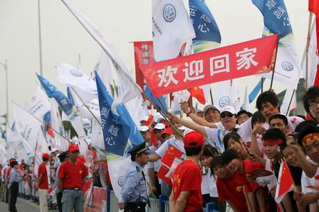"""齐集上海大众明星车型的大众汽车奥运会火炬接力车队来到上海,上海市民打出了""""欢迎回家""""的温馨标语,热烈欢迎火炬接力车队回到家乡"""