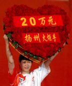 图文:奥运圣火在扬州传递 肖爱华展示爱心牌