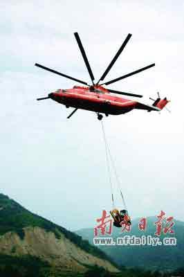世界最大的直升机米-26直升机正向唐家山堰塞湖坝顶吊运挖掘机。新华社发