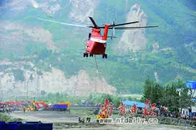 在北川县擂鼓镇,工作人员正准备吊运的大型机械。本报记者严明莫伟浓摄