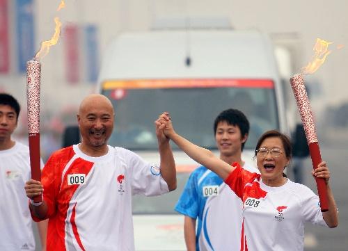 火炬手陈佩斯与上一棒火炬手白慧敏(右)在交接后握手致意
