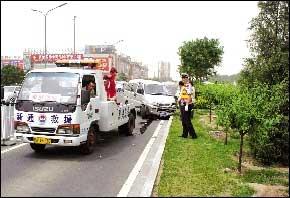 救援车正准备将撞毁的车辆拖走。 本报实习生 罗亮 摄