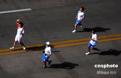 5月29日,奥运圣火开始在安徽淮南传递。图为第57号火炬手传递火炬。 中新社发 廖攀 摄