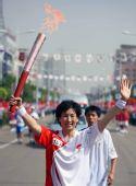 图文:奥运圣火在淮南传递 火炬手陈珍手持火炬
