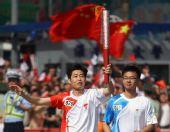 图文:奥运圣火在淮南传递 火炬手葛真手持火炬