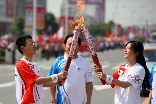 5月29日,奥运火炬手赵薇(右)与徐有忠在传递过程中交接。当日,北京奥运圣火在安徽芜湖传递。