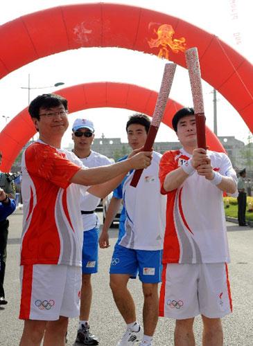 5月29日,奥运火炬手尹同耀(左)与娄祥武在传递过程中交接。当日,北京奥运圣火在安徽芜湖传递。