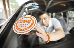 """昨日,在花都区政府,区府司机正在为公务车贴上""""文明号""""车标。邵权达摄"""