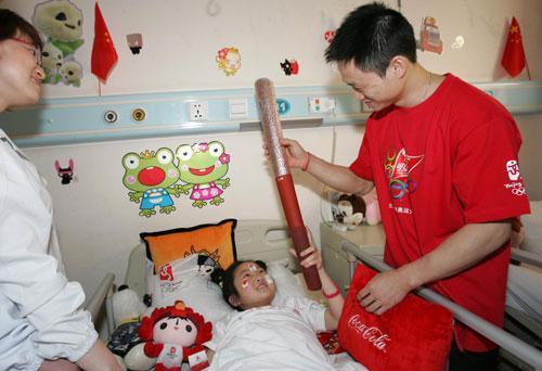 可口可乐火炬手将祥云火炬展示给受伤儿童