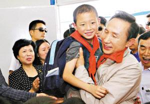 韩国总统李明博昨日在都江堰市幸福家园灾区群众安置点看望小学生。新华社 发