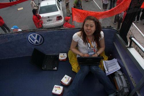 新华社记者李颖在由大巴改装的媒体车上工作,大众的LOGO就在旁边