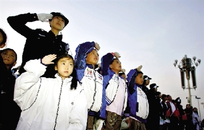 昨天,一名来自四川灾区的女学生认真地给国旗班战士系红领巾。