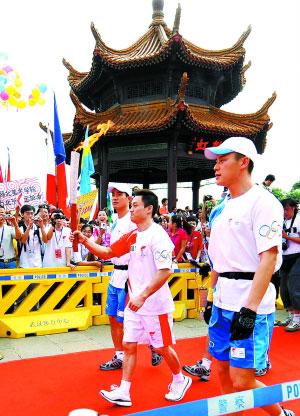 5月31日,奥运火炬手杨威(中)手持火炬传递。  新华社记者 程敏摄