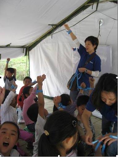 """诺基亚中国公司副总裁萧洁云带领志愿者和什邡""""二十米大街帐篷小学""""学生一起做游戏,共度六一儿童节。"""