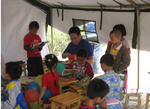 """诺基亚志愿者给什邡""""二十米大街帐篷小学""""的孩子们送去了图书。图为诺基亚西区总经理康亮给孩子们讲故事。"""