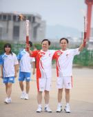 图文:奥运圣火在宜昌传递 陈红伟与郑联合交接