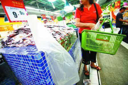 记者昨日在一家超市看到,不少市民无节制地取用手撕免费保鲜袋当作购物袋用。时报记者 杜翠 摄